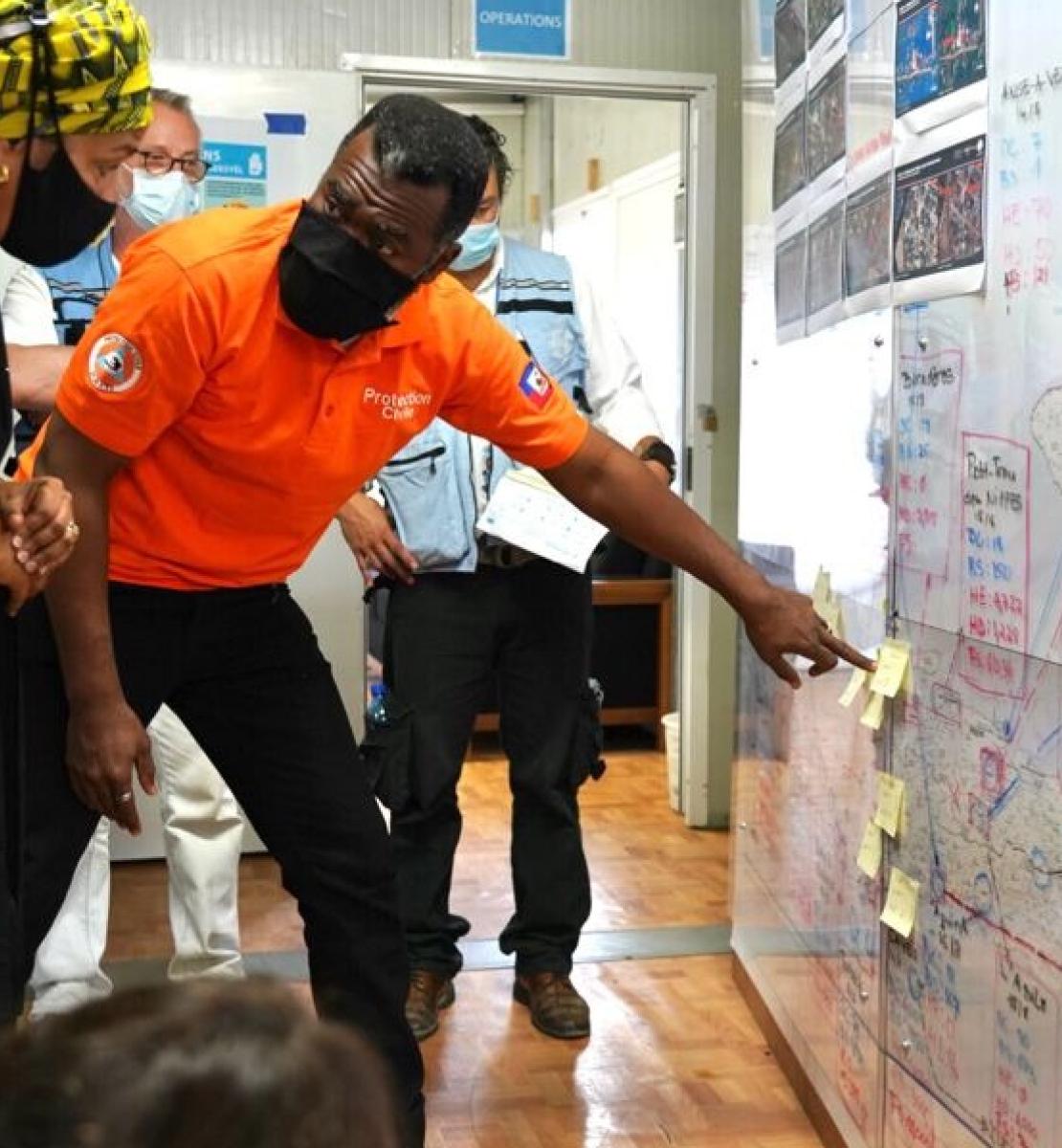 En Haïti, un membre de l'équipe de secours montre à la Vice-Secrétaire générale de l'ONU, Amina Mohammed, comment sont menées les opérations de secours.