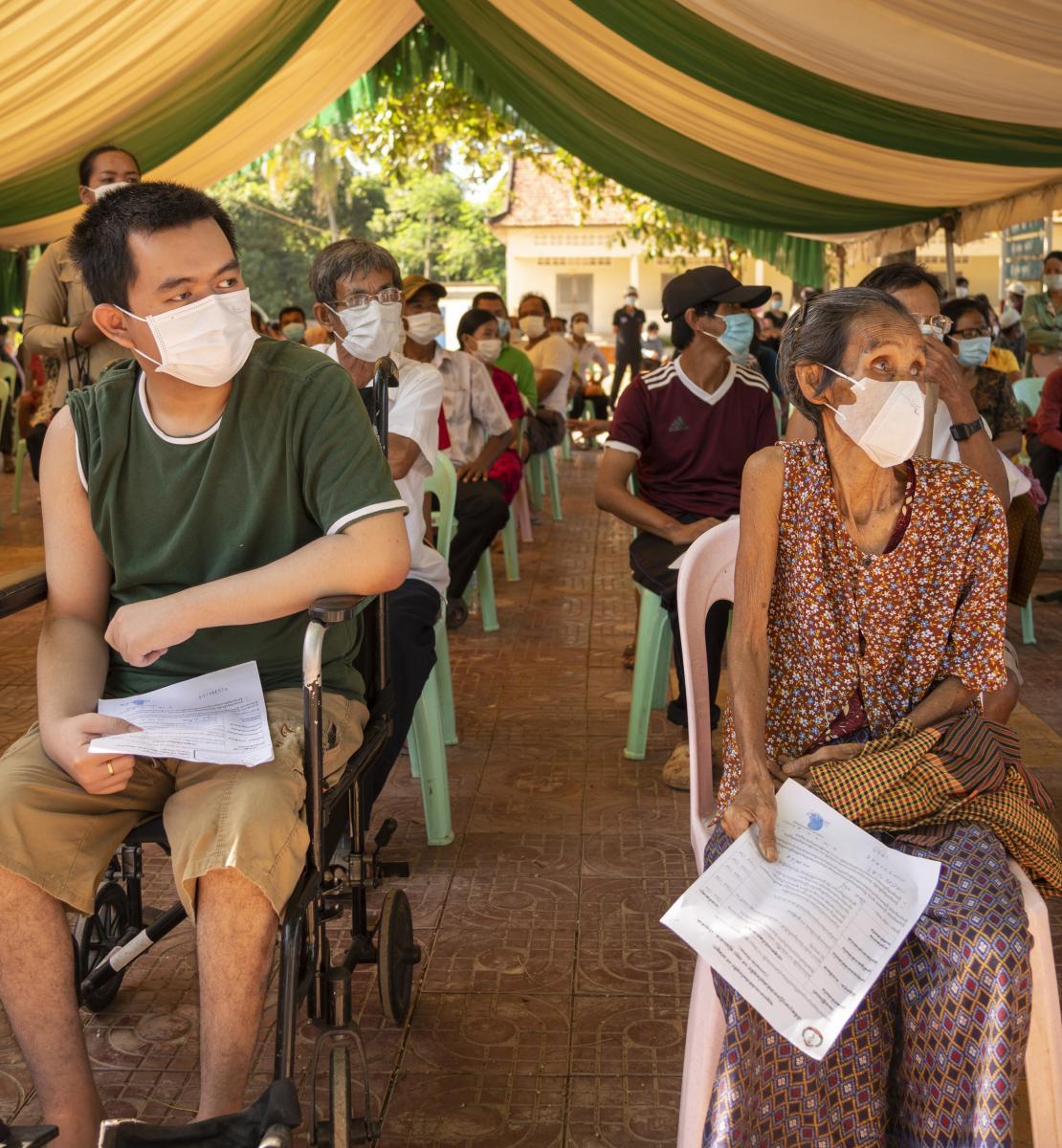 Des personnes âgées et des personnes handicapées portant un masque de protection respiratoire sont assises sur des chaises en plastique distantes les unes des autres, sous une grande tente géante installée en extérieur, en attendant de pouvoir se faire vacciner.