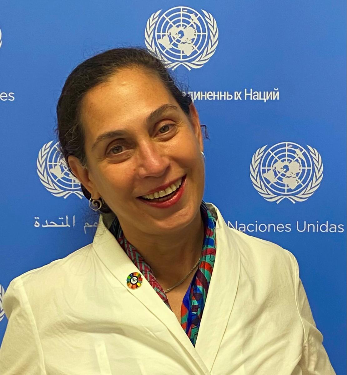 A woman in a yellow suit smiles at the camera in front of a blue and white United Nations sign.