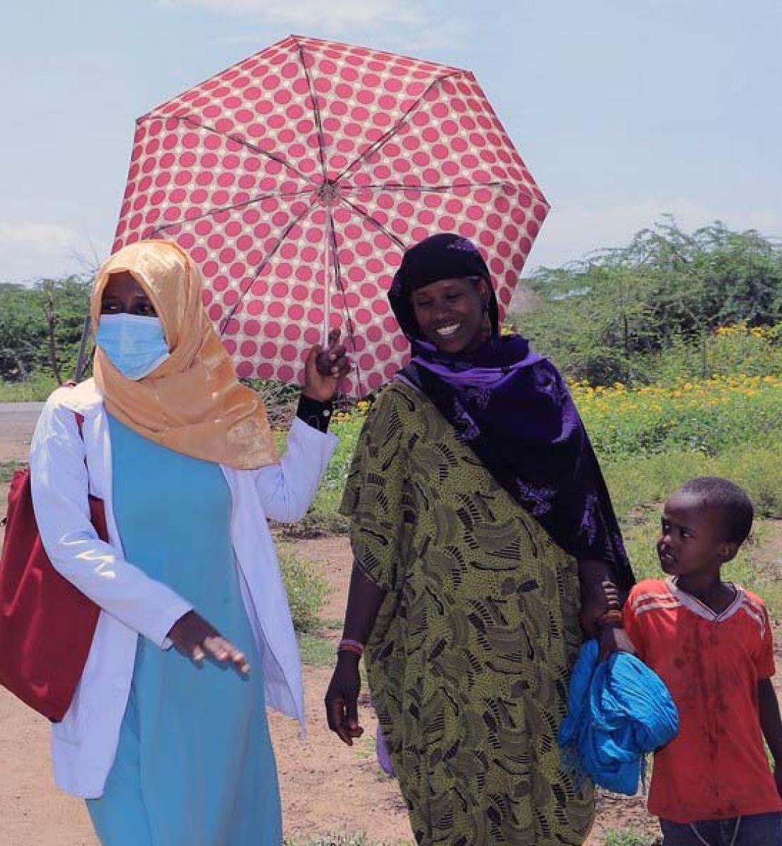 Una mujer con mascarilla sostiene un paraguas mientras camina junto a una mujer y su hijo.