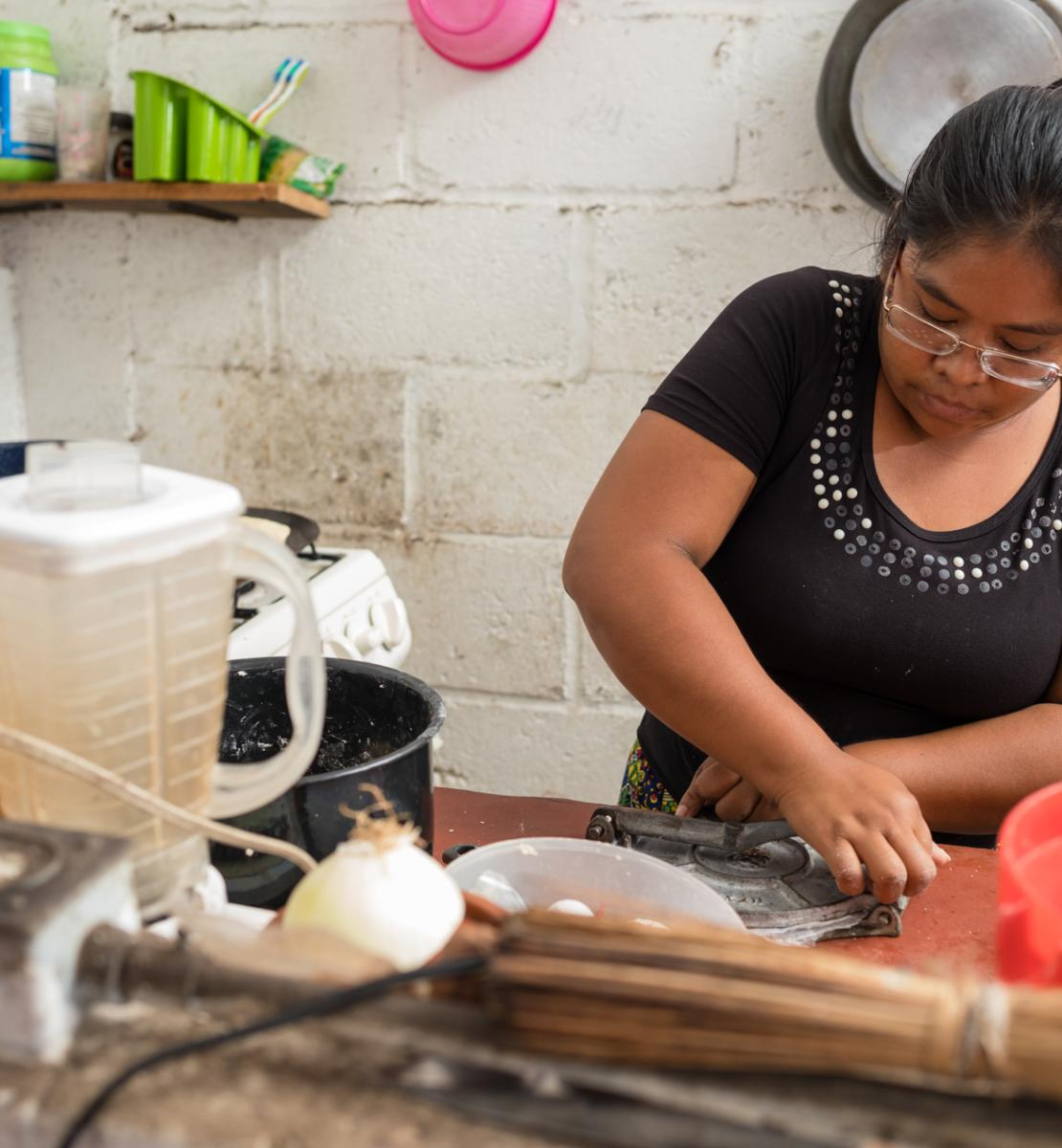 A woman in a black shirt cooks in a kitchen.
