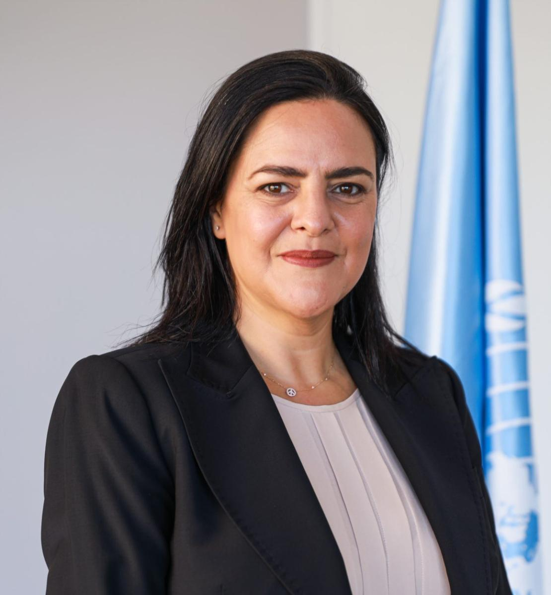 A woman in a black blazer looks straight into the camera with the United Nations flag behind her.