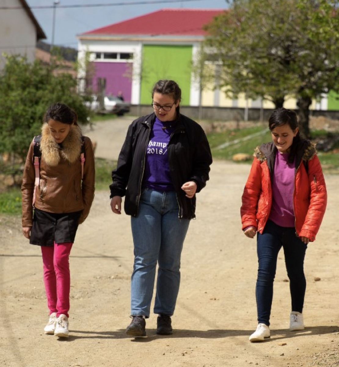 三个年轻女孩穿着夹克走在一条泥泞的路上。