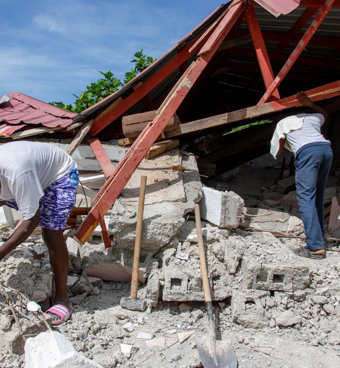 رجلان يتفحصان أنقاض مبنى منهار بعد الزلزال الذي بلغت قوته 7.2 درجة.