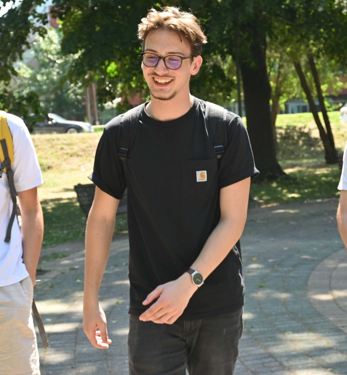 三个年轻人,泰奥(左)、欧尔罕(中)和鲍里斯(右),一起在公园里快乐地散步。