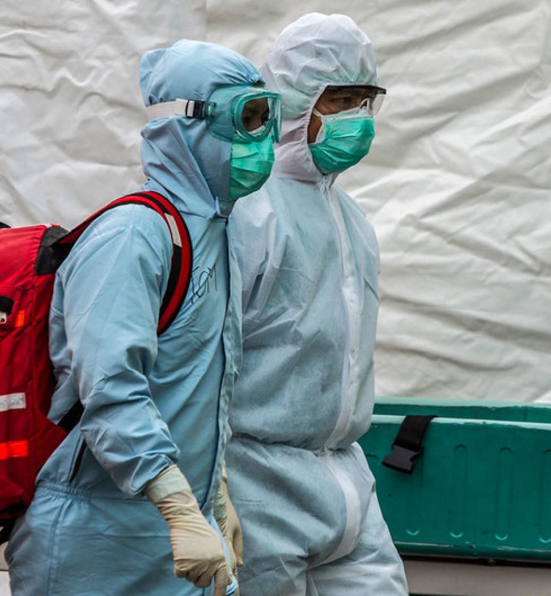 Dos trabajadores sanitarios con equipo de protección personal de cuerpo completo y mascarillas, caminan juntos y uno carga una gran mochila roja.