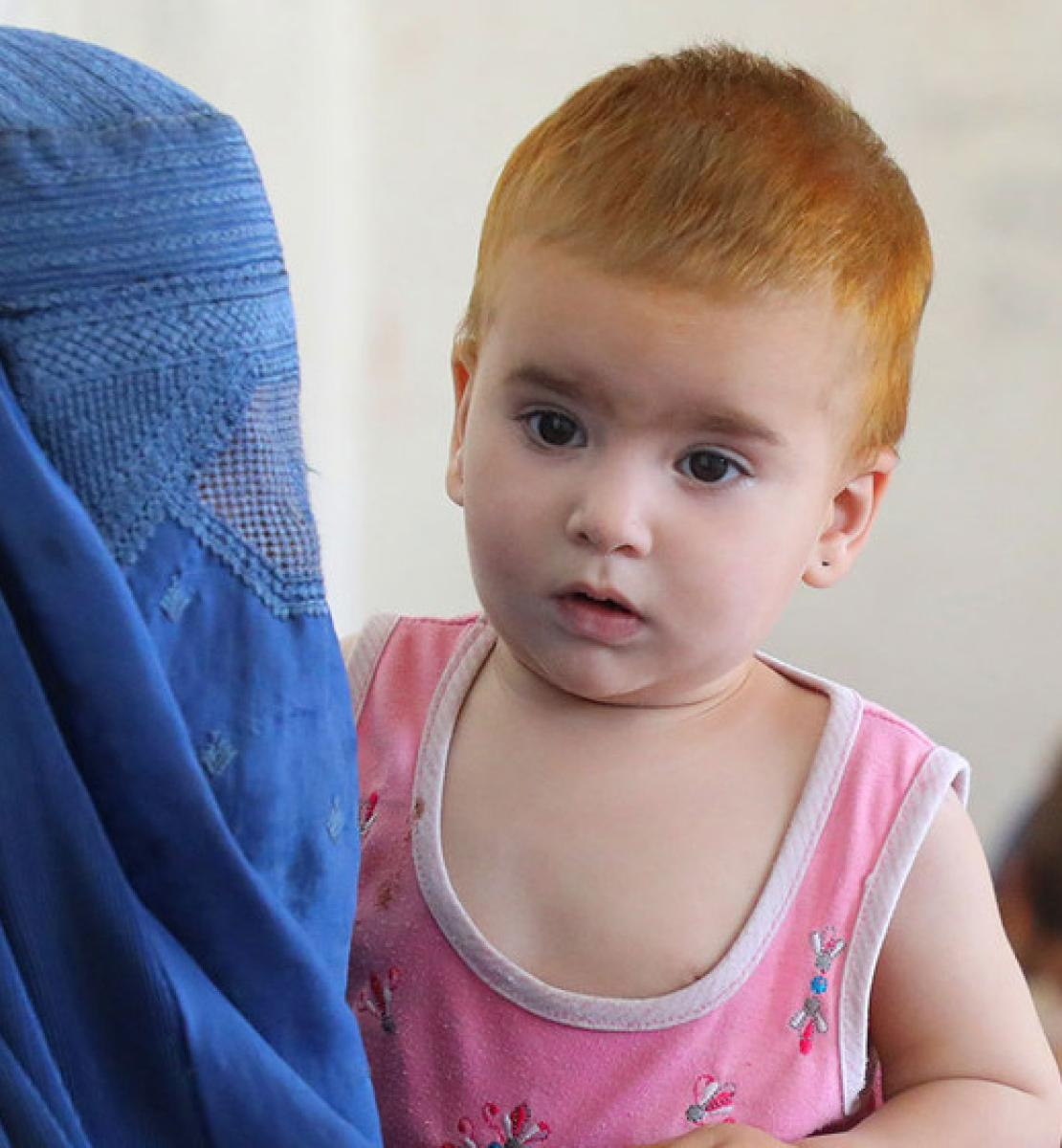 تظهر الأم في المقدمة وهي ترتدي غطاء الرأس والوجه وهي تحمل طفلها، وفي الخلفية أم وطفل آخر.