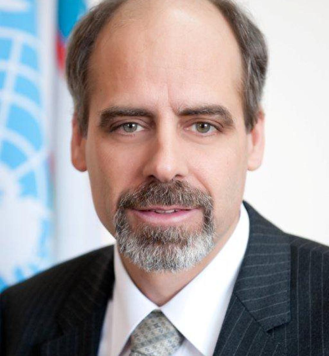 A headshot of a man looking straight into the camera with the flag from the United Nations in the background.