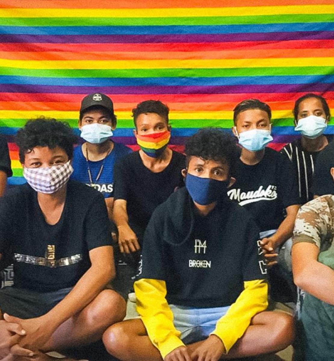 مجموعة من الشباب يرتدون كمامات يجلسون أمام علم بألوان قوس قزح.
