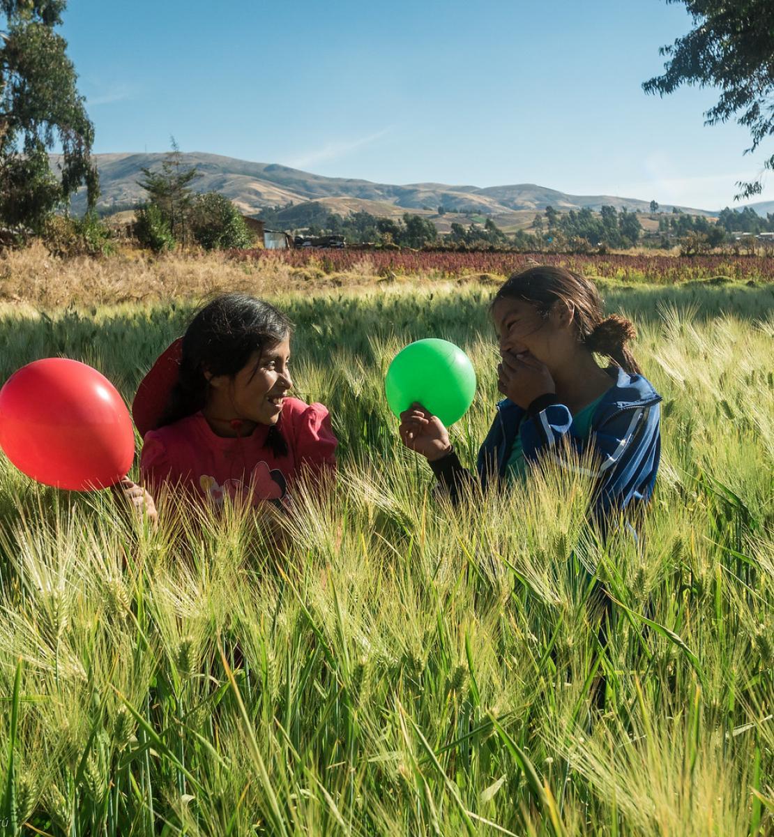 Deux petites filles jouent en riant avec un ballon vert et un ballon rouge dans un champ.