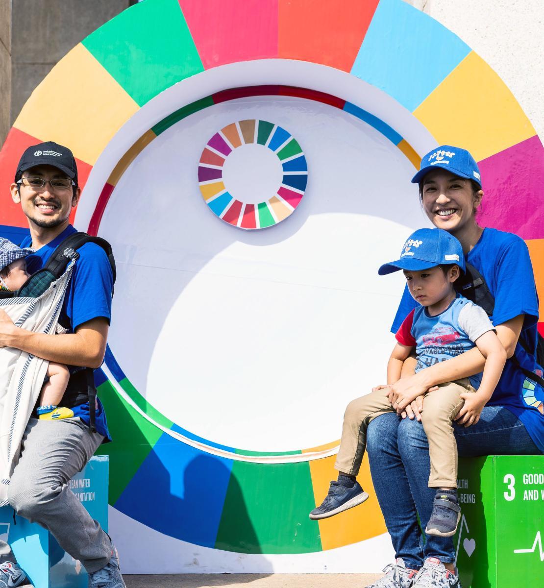 يحمل كل من الأب والأم طفلًا في أحضانهما بينما يبتسمان للكاميرا جالسين أمام عجلة أهداف التنمية المستدامة.