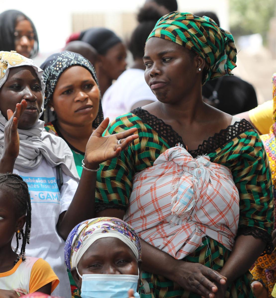 Varias mujeres y niñas conversando en la calle.