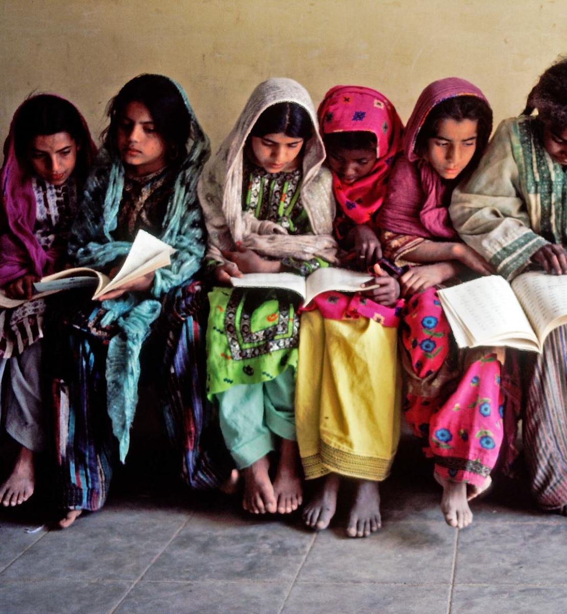 Several children dressed in bright colors look down at books.