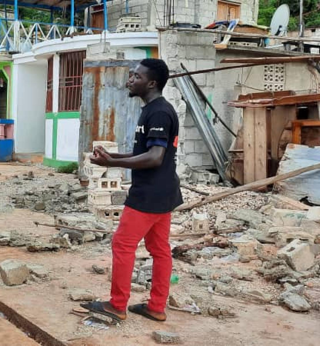 一个穿红裤子的年轻人在地震造成的废墟附近对一大群志愿者和援助人员讲话。