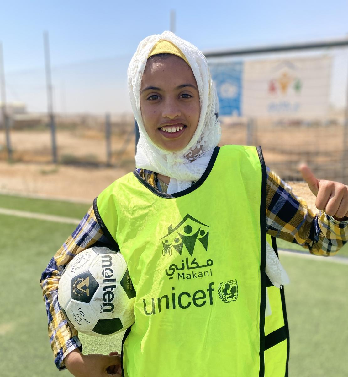 A smiling young girl holds a soccer ball in one arm and gives the camera a thumbs up with her other hand.