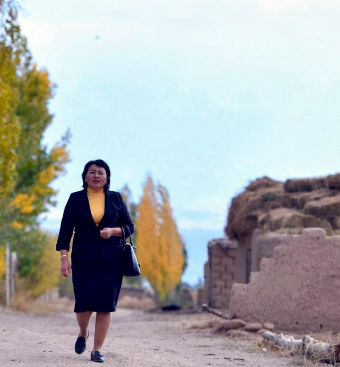 一个身穿黑色西装和黄色衬衫的女人昂首阔步走在路上。