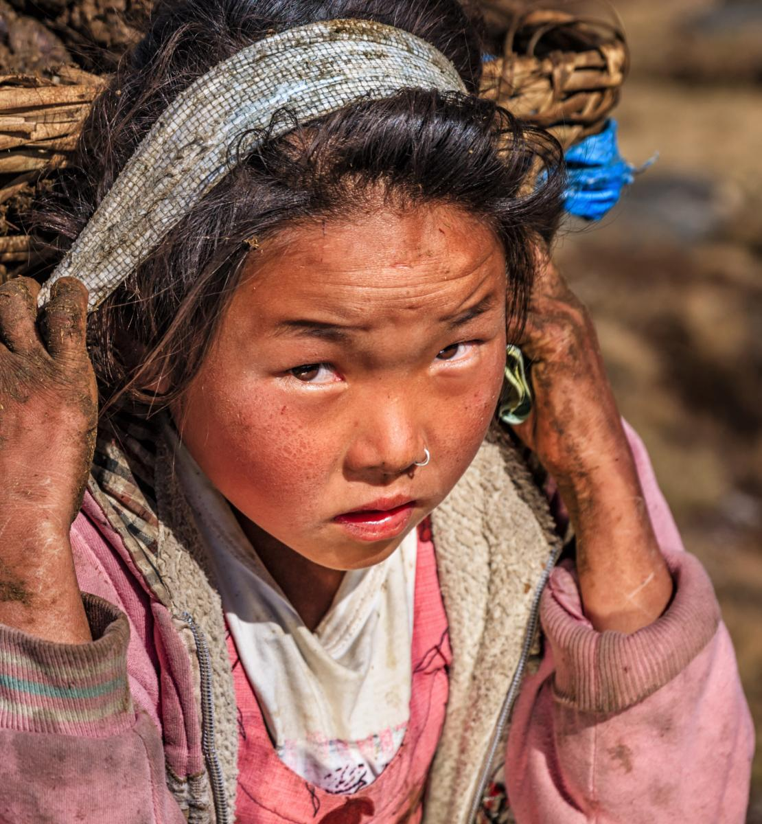 A young girl, with dirt on her hands and face, carries a large basket on her back.