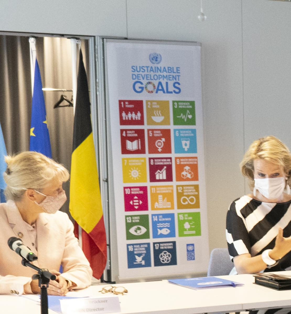 Director of the UN/UNDP Office in Brussels, and Her Majesty sit side-by-side at a desk in front of microphones.