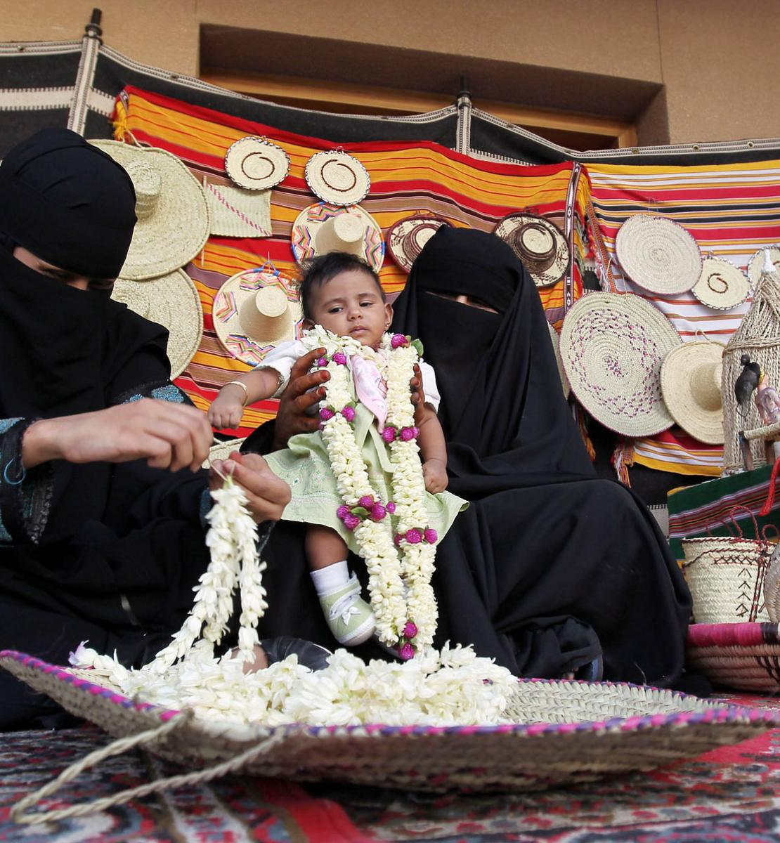 A Saudi woman sits on a rug and threads fresh flowers to sell in a souk as another woman sitting beside her holds up a baby.