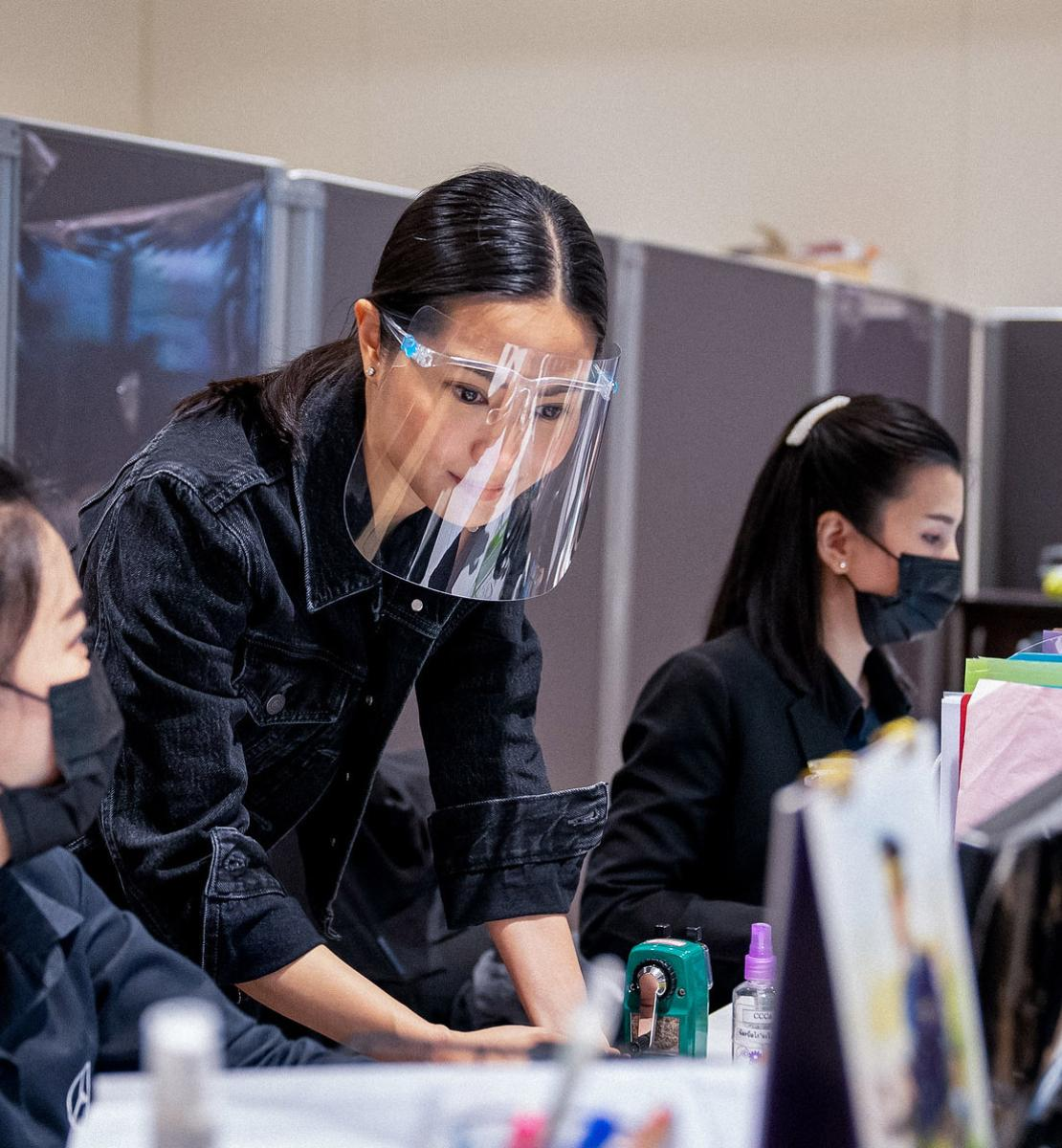 Women wearing protective masks and face shields work together at a desk at an office.