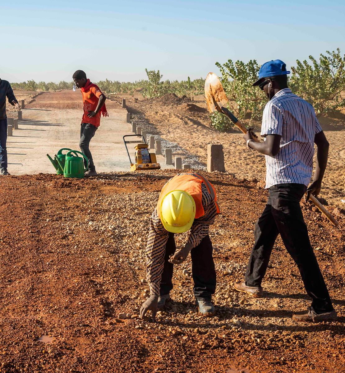 صورة لأربعة أشخاص يعملون في موقع بناء في الصحراء.