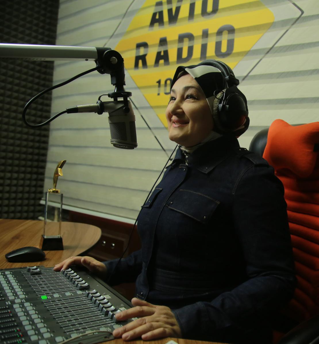 Una mujer vestida de negro se sienta en un escritorio con un micrófono y un equipo de radio.