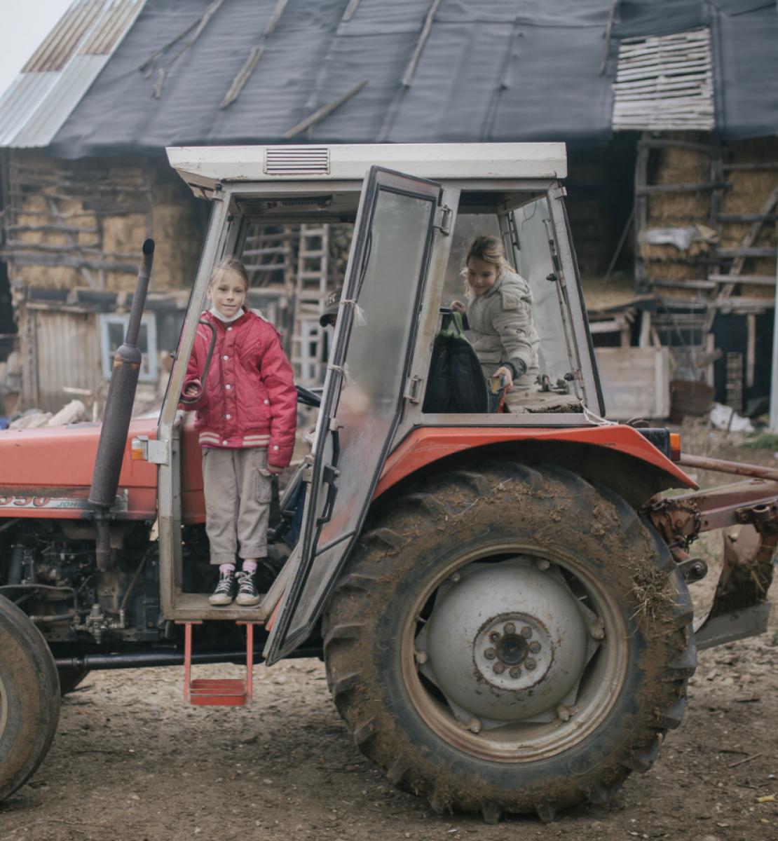 Dans une ferme, deux fillettes sont à bord d'un tracteur en panne.